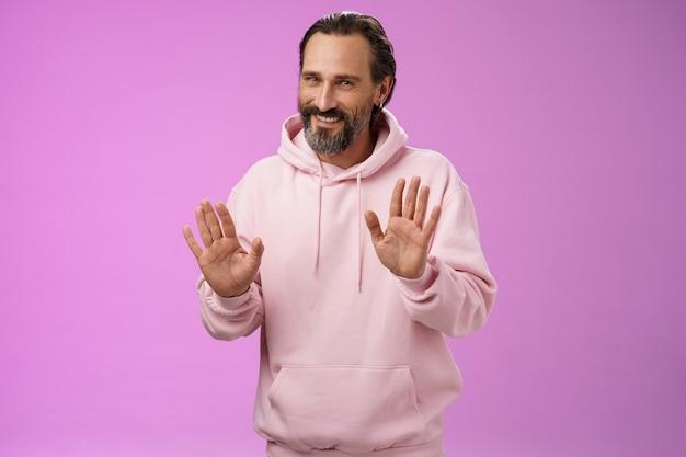 Non merci. charmant homme barbu adulte viril poli cheveux gris en sweat à capuche rose s'excusant de refus lever les paumes geste de rejet refusant l'offre souriante dire désolé pas intéressé, fond violet.
