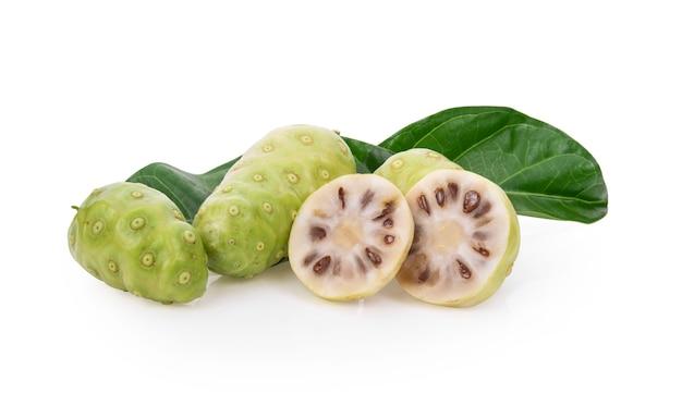 Noni ou morinda citrifolia fruits avec des tranches de feuilles vertes et isolés sur fond blanc