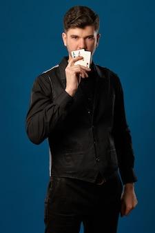 Noob au poker en pantalon gilet noir et chemise tenant deux cartes à jouer tout en posant contre des bleus ...