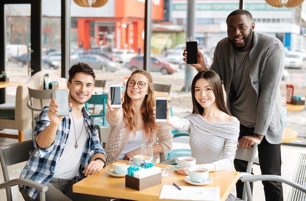 Nos meilleurs compagnons. des jeunes internationaux heureux montrent leurs smartphones modernes assis au café.