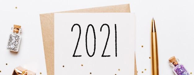 Note 2021 avec enveloppe, cadeaux et étoiles de paillettes d'or sur blanc.