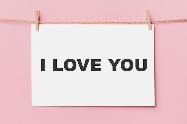 Note broche lettre sur corde sur fond rose, amour et concept de valentine je t'aime