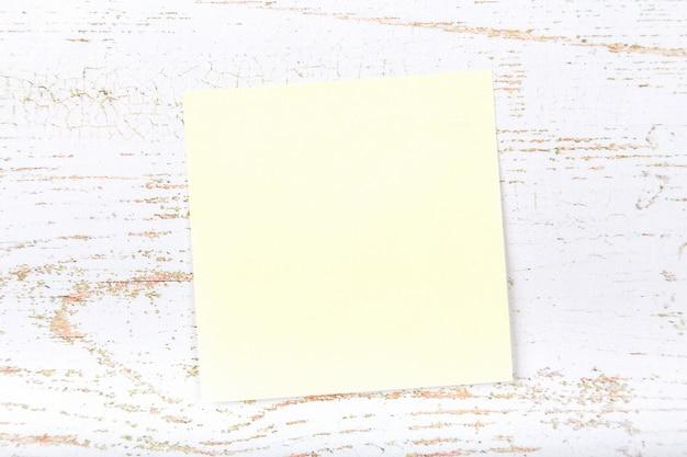 Note collante de papier vide sur bacpground en bois blanc avec espace de copie