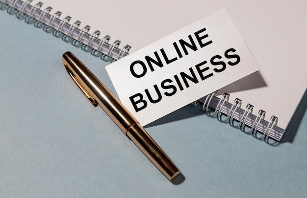 Note de concept d'entreprise internet d'affaires en ligne et stylo doré sur fond bleu gris