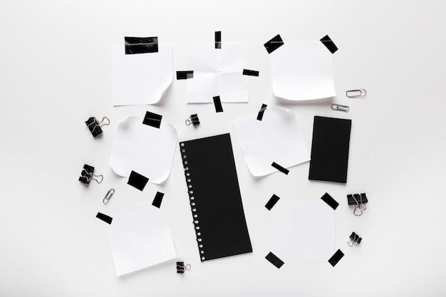 Note déchirée blanche, papier de cahier collé avec du ruban adhésif noir isolé sur blanc