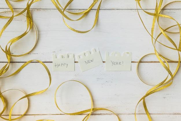 Note de félicitation de nouvel an se trouvant entouré d'un ruban