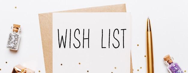 Note de liste de souhaits avec enveloppe, cadeaux et étoiles de paillettes d'or sur une surface blanche. joyeux noël et nouvel an concept