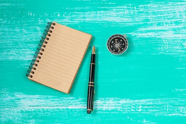 Note de livre, fontaine et boussole sur la couleur du bois vintage