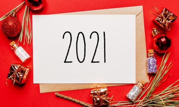 Note de noël 2021 avec cadeau, branche de sapin et jouet sur rouge