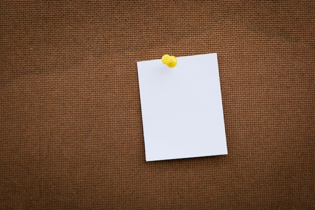 Note de papier blanc vierge épinglé sur un tableau en liège avec des punaises blanches, espace de copie disponible