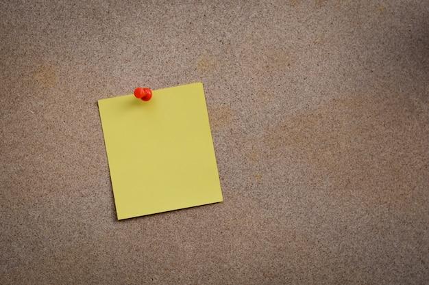Note de papier jaune vierge épinglé sur un tableau en liège avec des punaises blanches, espace de copie disponible