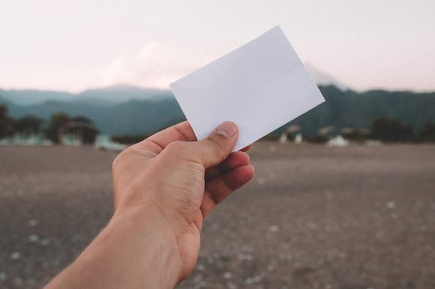 Note de papier vide dans la main à fond de paysage étonnant. concept de voyage et de vacances.