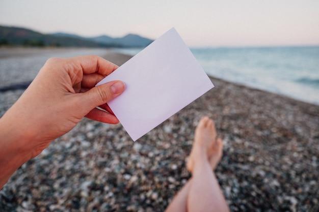 Note de papier vide à la main sur fond de paysage incroyable. concept de voyage et de vacances. feuille de papier blanc sans texte.