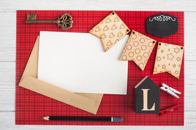 Note de papier vierge, enveloppe artisanale sur rouge