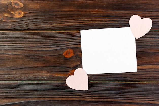 Note de papier vierge avec forme de coeur sur fond en bois grunge