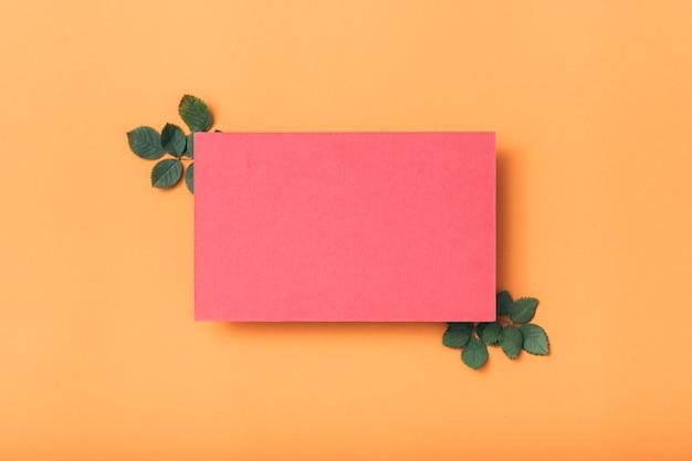 Note de papier vierge rose ou carte avec décor de feuilles vertes.