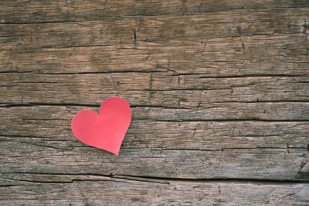 Note de papier vierge rouge avec forme de coeur sur fond en bois grunge