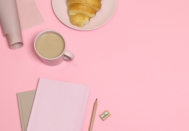Note rose avec crayon et taille-crayon, tasse à café, gâteau sur fond rose