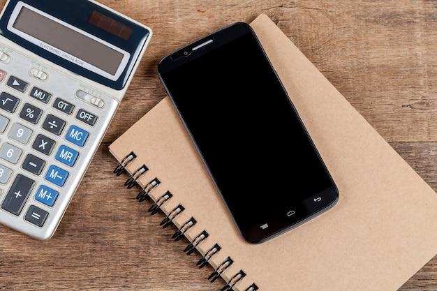 Note de téléphone portable et livre dans le bureau en bois vintage.