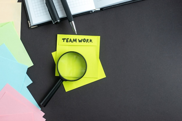Note de travail d'équipe vue de dessus avec des stylos autocollants et loupe sur fond sombre