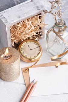 Note vide vide et enveloppe artisanale, bougie allumée dorée et ruban festif serti d'un décor en or.