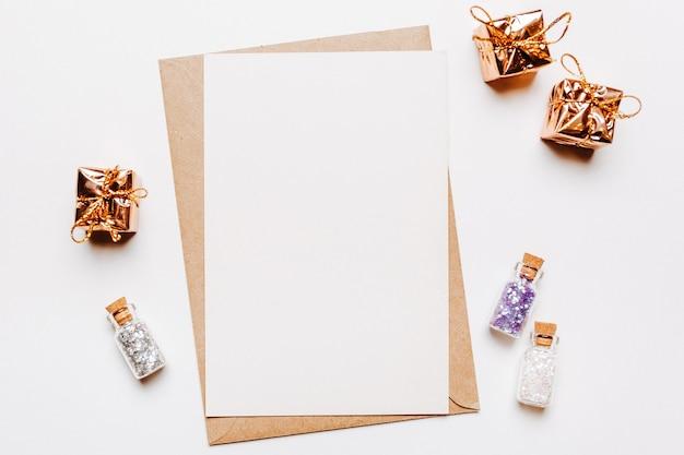 Note vierge avec des cadeaux et des paillettes sur fond blanc