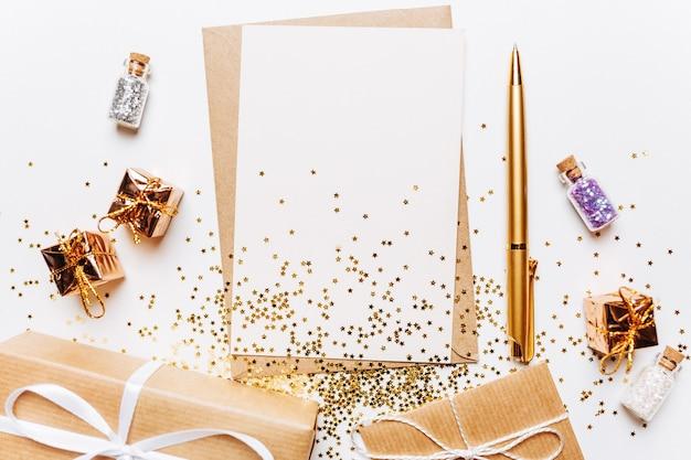 Note vierge avec des cadeaux, un stylo et des paillettes sur fond blanc