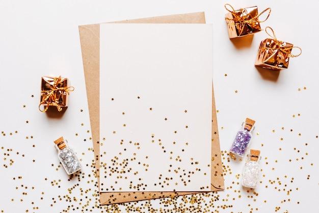 Note vierge avec enveloppe, cadeaux et étoiles de paillettes d'or sur blanc