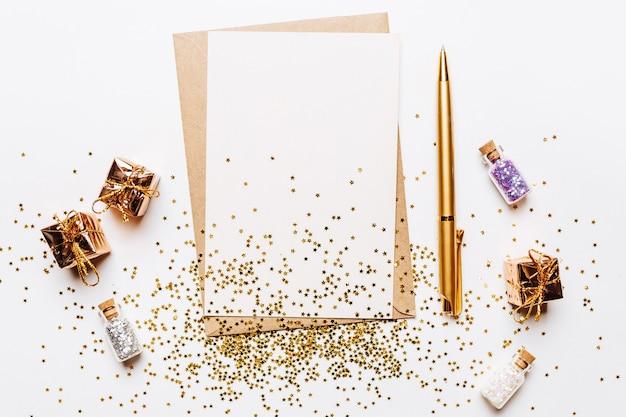 Note vierge avec enveloppe, cadeaux, stylo et étoiles de paillettes d'or sur fond blanc