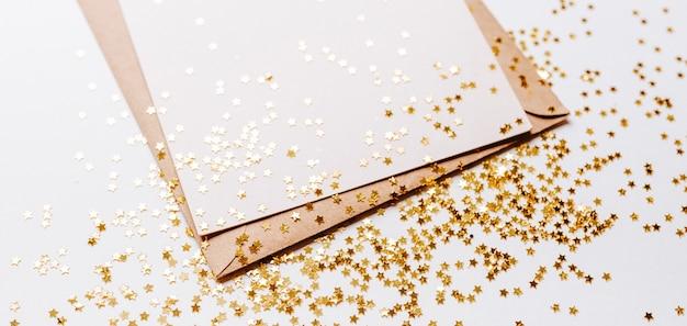 Note vierge avec enveloppe et étoiles de paillettes d'or sur blanc