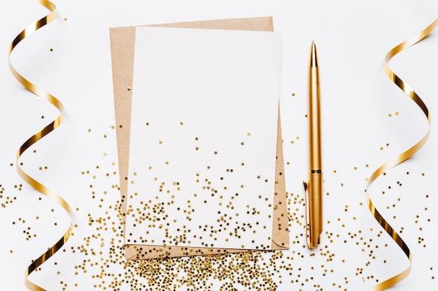 Note vierge avec enveloppe, ruban, confettis, stylo et étoiles de paillettes d'or sur blanc