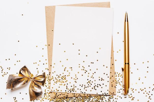 Note vierge avec enveloppe, stylo et étoiles de paillettes d'or sur fond blanc