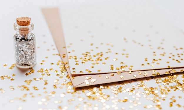 Note vierge avec des étoiles de paillettes d'or sur fond blanc
