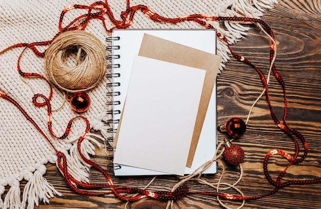 Note vierge sur fond en bois et tricoté. joyeux noël et nouvel an concept