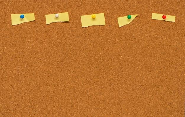 Note vierge jaune sur panneau de liège avec chemin de détourage.