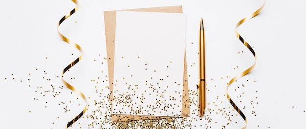 Note vierge avec ruban, stylo et paillettes d'or sur fond blanc