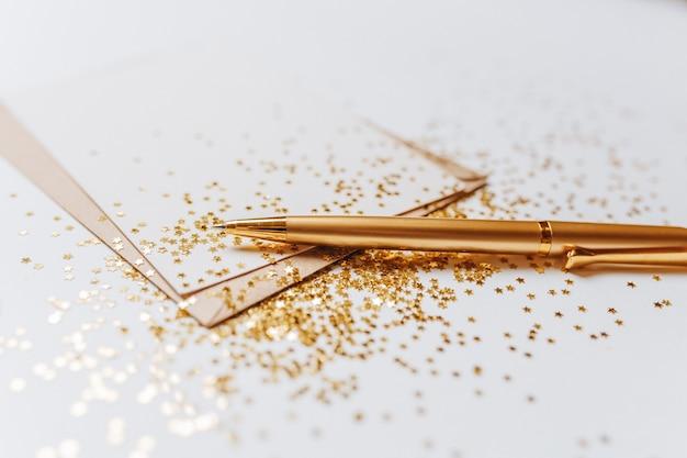 Note vierge avec stylo et étoiles de paillettes d'or
