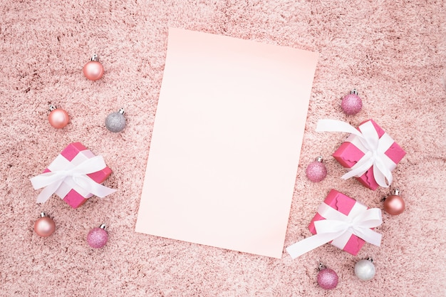 Note de voeux avec des boîtes de cadeau de noël et des balles sur un tapis texturé rose
