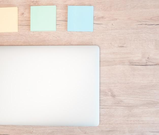 Notes autocollantes et un ordinateur portable blanc sur la table