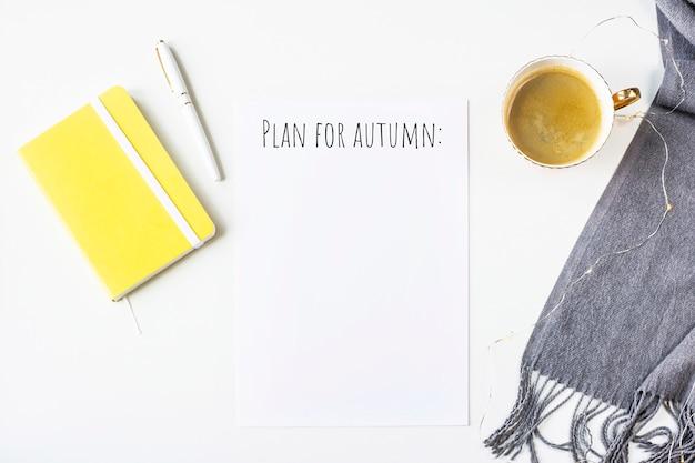 Notes d'automne sur une table blanche à côté d'un foulard, bloc-notes jaune