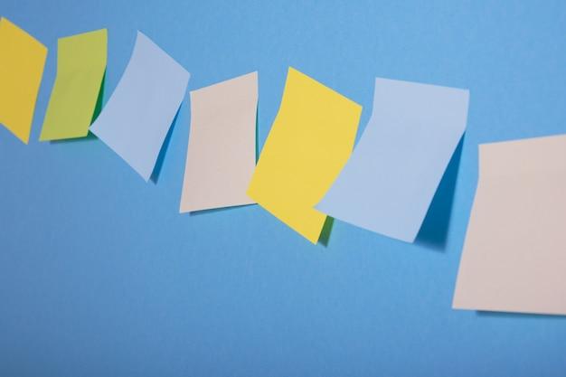 Notes collantes de couleur vive sur fond bleu d'affilée, mise au point sélective