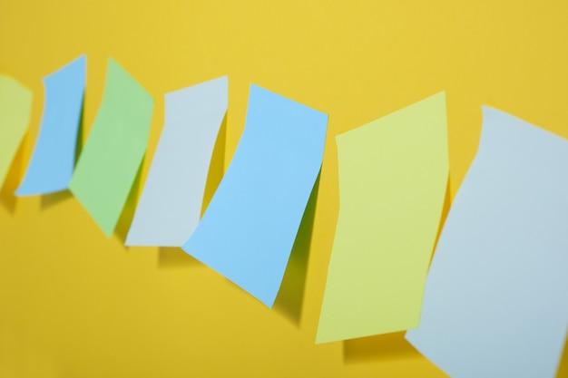 Notes collantes de couleur vive sur fond jaune d'affilée, espace de copie, mise au point sélective