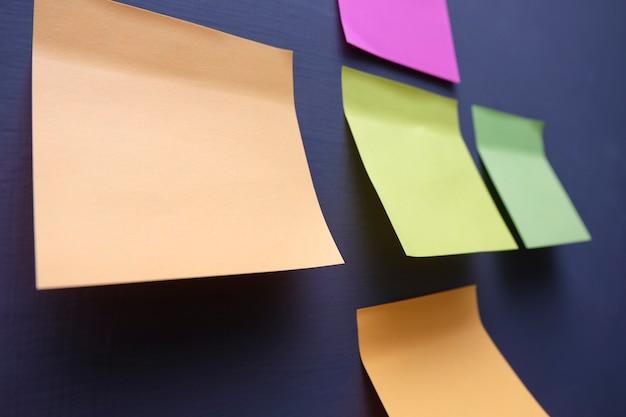 Notes collantes multi couleur sur le bureau de mur gris