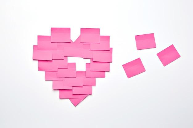 Notes collantes roses vierges collées sur un mur blanc en forme de coeur