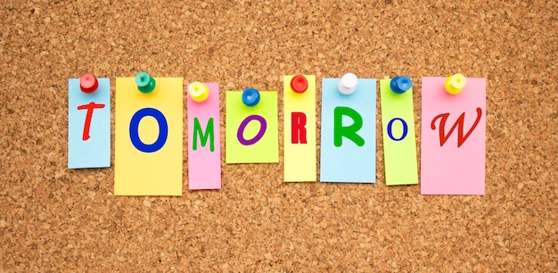 Notes de couleur avec des lettres épinglées sur un panneau de liège. le mot demain.