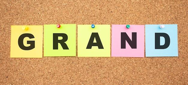 Notes multicolores avec des lettres épinglées sur un panneau de liège mot grand