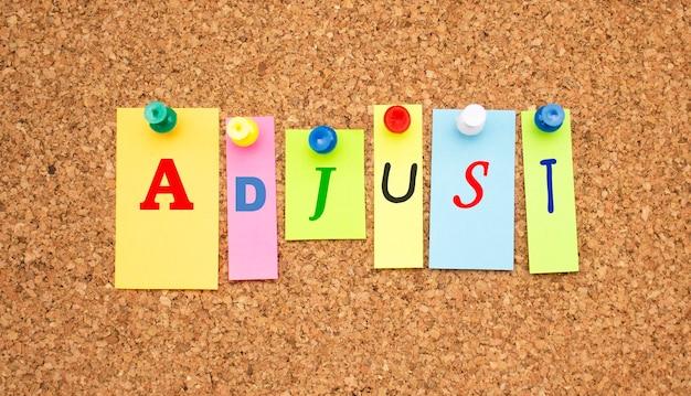 Notes multicolores avec des lettres épinglées sur un panneau de liège. word adjust.