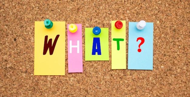 Notes multicolores avec des lettres épinglées sur un panneau de liège word quoi