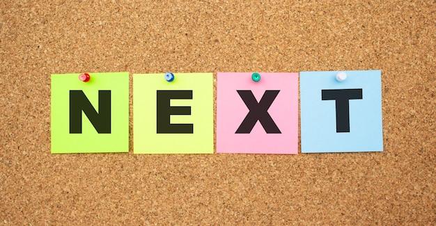 Notes multicolores avec des lettres épinglées sur un tableau d'affichage en liège