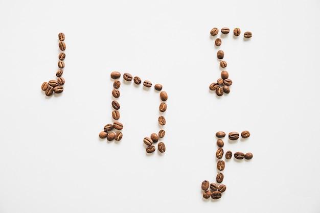 Notes de musique faites avec des grains de café torréfiés isolés sur fond blanc